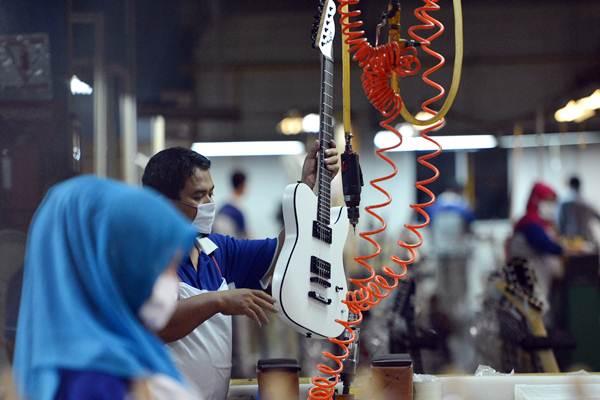 Pekerja menyelesaikan pembuatan gitar listrik di pabrik alat musik Cileungsi, Kabupaten Bogor, Jawa Barat, Selasa (27/3/2018). - ANTARA/Wahyu Putro A