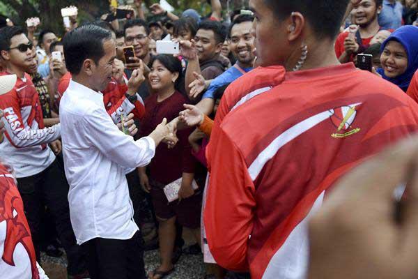 Presiden Joko Widodo (tengah)menyalami warga ketika mengunjungi Pusat Primata Schmutzer di Kebun Binatang Ragunan Jakarta, Kamis (29/6). - ANTARA/Wahyu Putro A