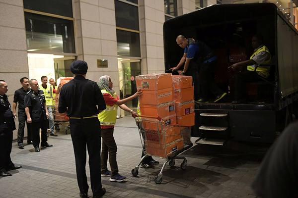 Perwira polisi Malaysia mendorong troli selama penggerebekan tiga apartemen di sebuah kondominum yang dimiliki oleh keluarga mantan perdana menteri Malaysia Najib Razak, di Kuala Lumpur, Malaysia, Kamis (17/5). - Reuters