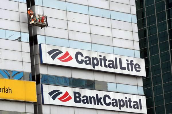 Pekerja membersihkan kaca gedung bertingkat di dekat logo PT Capital Life Indonesia di Jakarta, Kamis (21/6/2018). - JIBI/Dedi Gunawan