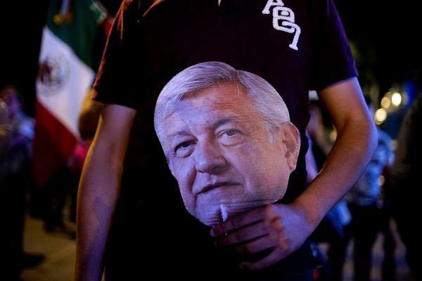 Pendukung Andres Manuel Lopez Obrador membawa topeng calon presiden Meksiko tersebut ketika menunggu hasil Pilpres di Mexico City, Meksiko, Minggu (1/7). - Reuters/Alexandre Meneghini