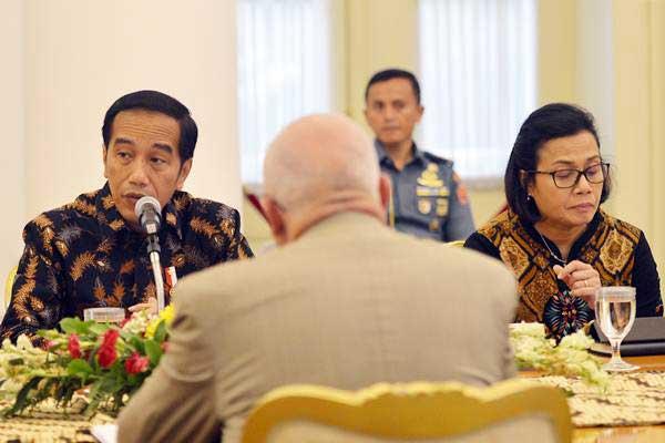 Presiden Joko Widodo (kiri) didampingi Menteri Keuangan Sri Mulyani menyampaikan paparan ketika menerima delegasi Asian Infrastructure Investment Bank (AIIB) di Istana Kepresidenan Bogor, Jawa Barat, Senin (12/3/2018). - ANTARA/Wahyu Putro A