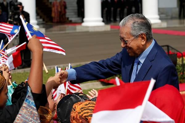 Perdana Menteri Malaysia Mahathir Muhamad menyalami para pelajar, di sela-sela upacara penyambutannya di Istana Bogor, Jawa Barat, Jumat (29/6/2018). - Reuters/Darren Whiteside