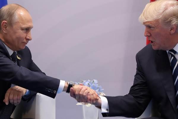 Presiden AS Donald Trump (kanan) bersalaman dengan Presiden Rusia Vladimir Putin (kiri) saat keduanya melakukan pertemuan bilateran di sela KTT G20 di Hamburg, Jerman, Juli 2017. - Reuters/Carlos Barria