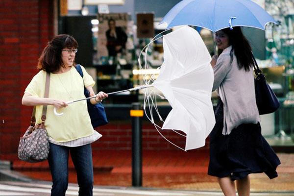 Dua pejalan kaki menggunakan payung berjuang melawan hujan lebat dan angin saat Topan Jongdari mendekati daratan Jepang di Tokyo, Jepang, (Sabtu/28/7/2018). - Reuters/Issei Kato