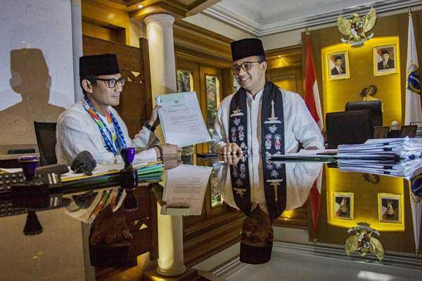 Gubernur DKI Jakarta Anies Baswedan (kanan) dan Sandiaga Uno (kiri) menunjukkan surat pengunduran diri Sandiaga sebagai Wagub DKI Jakarta di Balai Kota, Jakarta, Jumat (10/8/2018). - ANTARA/Galih Pradipta