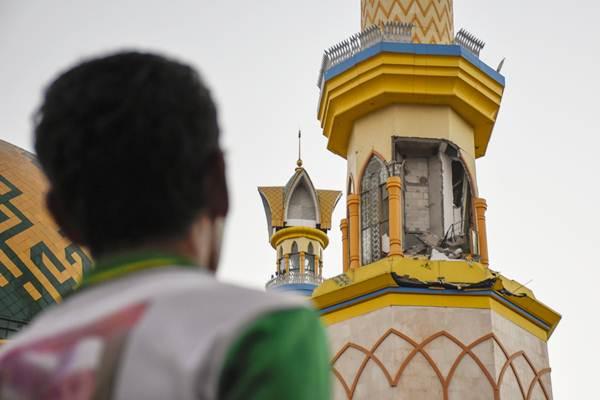 Warga mengamati menara Islamic Center Hubbul Wathan yang dindingnya sebagian roboh pascagempa bumi di Mataram, NTB, Senin (6/8/2018). - ANTARA/Ahmad Subaidi