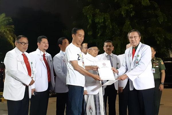Ketua Umum Ikatan Dokter Indonesia (IDI) Ilham Oetama Marsis menyerahkan surat tanda selesai pemeriksaan kepada Presiden Joko Widodo di RSPAD Gatot Soebroto, Minggu (12/8/2018) - Bisnis/Amanda Kusumawardhani