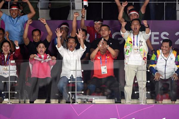 Ekspresi Presiden Joko Widodo (ketiga kiri), didampingi Ibu Negara Iriana Joko Widodo (kedua kiri), Menteri Menteri Koordinator Bidang Pembangunan Manusia dan Kebudayaan Puan Maharani (kiri), Menteri Koordinator Bidang Politik, Hukum, dan Keamanan Wiranto (ketiga kanan), Menteri Pemuda dan Olahraga Imam Nahrawi (kedua kanan), dan Menteri Koordinator Bidang Kemaritiman Luhut Binsar Pandjaitan, saat menonton laga final bulu tangkis beregu putra Asian Games 2018, pada Rabu (22/8/2018) - Bisnis/Dwi Prasetya