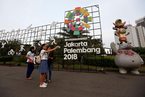 Warga berfoto di depan logo Asian Games 2018 di Jakarta. - Reuters