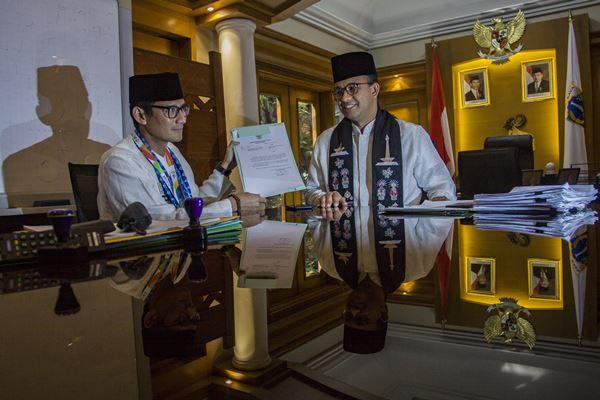 Gubernur DKI Jakarta Anies Baswedan (kanan) dan Sandiaga Uno (kiri) menunjukkan surat pengunduran diri Sandiaga sebagai Wagub DKI Jakarta di Balai Kota, Jakarta, Jumat (10/8).  - Antara