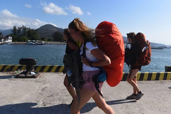 Wisatawan mancanegara meninggalkan Pelabuhan Bangsal usai dievakuasi dari Gili Trawangan di Pelabuhan Bangsal, Lombok Utara, NTB, Senin (6/8). Sedikitnya 700 orang wisatawan bersama warga setempat dievakuasi dari Gili Trawangan, Gili Air dan Gili Meno menuju Pelabuhan Bangsal mengantisipasi terjadinya gempa susulan.  - Antara