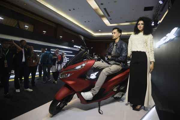 Model berada di atas sepeda motor All New Honda PCX produksi Indonesia saat peluncuran pemasarannya di Jakarta, Rabu (7/2). Skutik premium Honda terbaru dengan sejumlah pembaharuan dan fitur baru seperti full digital panel meter serta smart key system tersebut dipasarkan dengan harga Rp27,7 juta untuk tipe CBS dan Rp30,7 juta tipe ABS on the road Jakarta.  - ANTARA