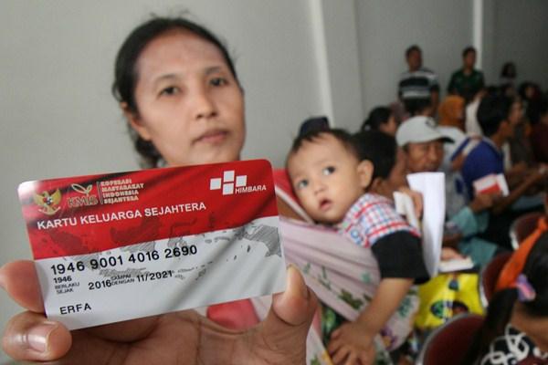Warga memerlihatkan Kartu Keluarga Sejahtera saat pencairan Bantuan Pangan Nontunai di Surabaya, Jawa Timur, Jumat (24/2). - Antara/Didik Suhartono