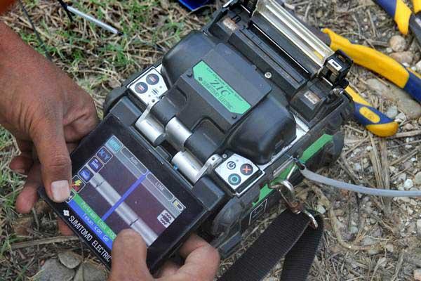 Petugas melakukan penyambungan kabel fiber optik Indihome dengan menggunakan alat 'splicer' di Desa Seuneubok Teungoh, Idi Rayeuk, Aceh Timur, Aceh, Senin (11/12). - ANTARA/Syifa Yulinnas