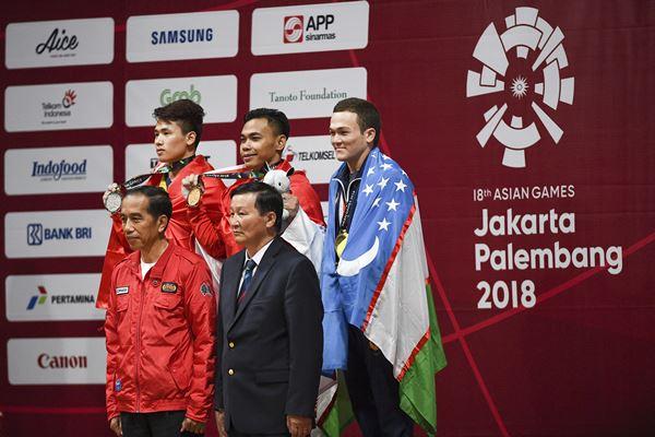 Presiden Joko Widodo (kiri bawah) berfoto bersama Lifter Indonesia peraih medali emas Eko Yuli Irawan (tengah atas), Lifter Vietnam Van Vinh Trinh (kiri atas) dan Lifter Uzbekistan Adkhamjon Ergashev (kanan atas) berfoto bersama pada upacara penyerahan medali angkat besi putra 62 kg Asian Games ke-18 2018 di JiExpo, Jakarta, Selasa (21/8).  - Antara