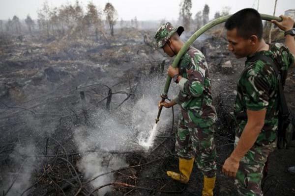 Dua anggota TNI memadamkan api yang disebabkan kebakaran hutan di Pulang Pisau, Kalimantan Tengah - Reuters/Darren Whiteside