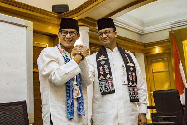Gubernur DKI Jakarta Anies Baswedan (kanan) berjabat tangan dengan Sandiaga Uno (kiri) usai pengunduran diri Sandiaga sebagai Wagub DKI Jakarta di Balai Kota, Jakarta, Jumat (10/8/2018). - ANTARA/Galih Pradipta