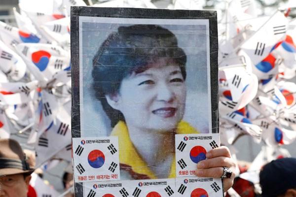Pendukung presiden Korea Selatan dimakzulkan Park Geun-hye membawa foto Park dalam aksi di depan kantor jaksa di Seoul, Korea Selatan. - Reuters