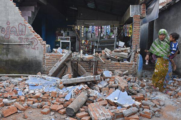 Seorang perempuan melintas dekat kios yang temboknya roboh pascagempa bumi di Dusun Lendang Bajur, Kecamatan Gunungsari, Lombok Barat, NTB, Senin (6/8). Badan Penanggulangan Bencana Daerah (BPBD) Nusa Tenggara Barat (NTB) mendapatkan laporan sementara jumlah korban meninggal dunia akibat gempa bumi berkekuatan 7 Skala Richter sampai dengan pukul 03.20 Wita Senin 6 Agustus 2018 sebanyak 82 orang. - Antara