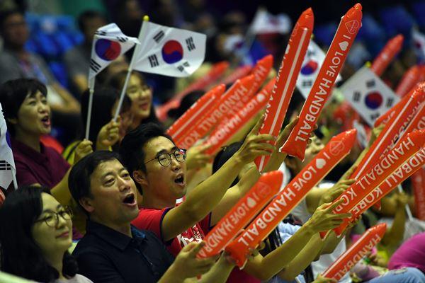 Suporter bola tangan Korea Selatan meneriakkan yel, yel sambil mengibarkan bendera negaranya saat pertandingan melawan Kazakhstan pada babak penyisihan grup A, Asian Games 2018 di GOR Popki Cibubur, Jakarta Timur, Kamis (23/8). - Antara