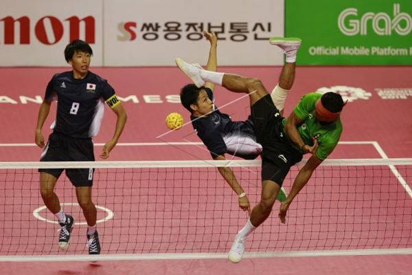 Pemain sepak takraw putra Indoneisa Husni Uba (kanan) menendang bola ke arah pemain Jepang Marashiro Yamada (tengah) dan Hirokazu Kobayashi (kiri). - Antara