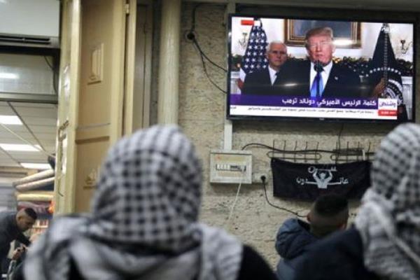 Warga Palestina menonton televisi menyiarkan Presiden Amerika Serikat (AS) Donald Trump berpidato di mana dia diharapkan mengumumkan bahwa AS mengakui Yerusalem sebagai ibu kota Israel, di Kota Tua Yerusalem, Rabu (6/12/2017).  - Reuters
