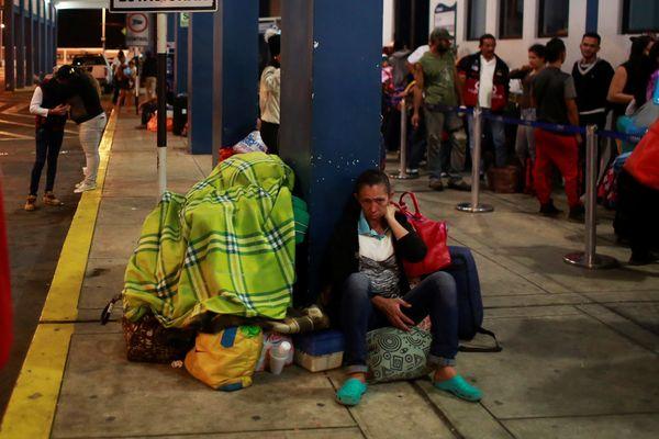 Pengungsi Venezuela duduk di luar kantor layanan perbatasan Binational Border Service Center Peru, di perbatasan dengan Ekuador, di Tumbes, Peru, Jumat (24/8). - Reuters/Douglas Juarez