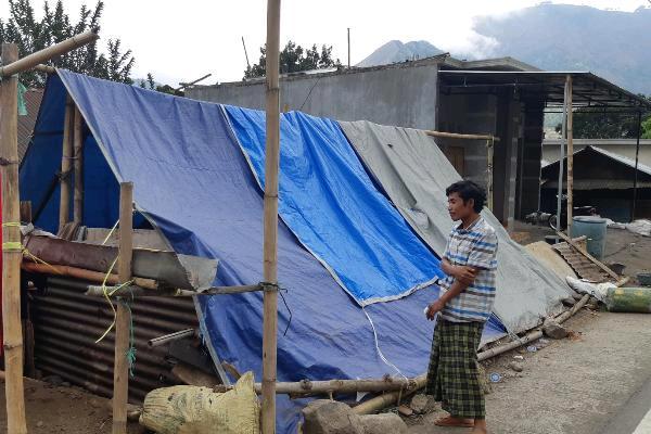 Nasri berdiri di samping tenda darurat yang didirikan sejak 29 Juli 2018. Tenda ini berkapasitas 12 orang, berada di Dusun Bebante, Desa Sembalun Bumbung, Kecamatan Sembalun, Lombok. (Novita Sari Simamora - Bisnis).