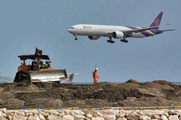 Pekerja beraktivitas di proyek perluasan apron Bandara Internasional I Gusti Ngurah Rai, Bali, Senin (16/7/2018). - ANTARA/Fikri Yusuf
