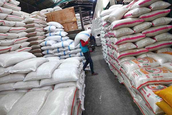 Pekerja memikul karung beras di Pasar Induk Beras Cipinang, Jakarta Timur, Jumat (19/1). - ANTARA/Sigid Kurniawan
