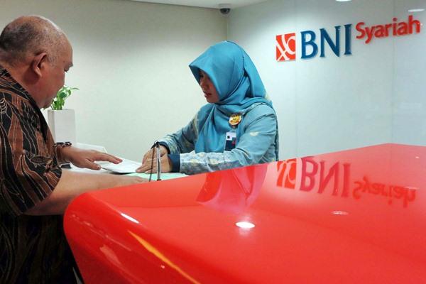 Karyawati PT Bank Negara Indonesia (BNI) Syariah melayani nasabah. - JIBI/Nurul Hidayat