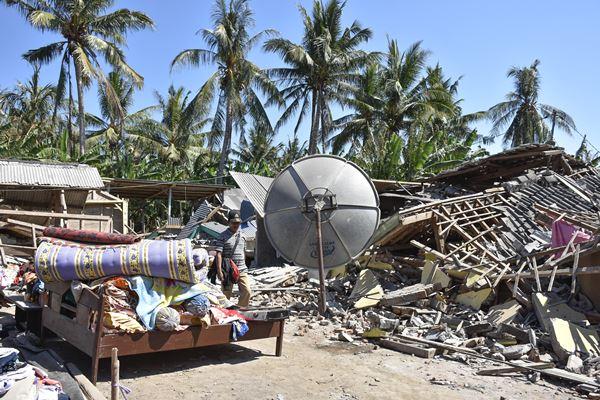 Seorang warga berada dekat puing-puing rumahnya yang roboh pascagempa di Dusun Labuan Pandan Tengak, Desa Padak Guar, Kecamatan Sambelia, Lombok Timur, NTB, Senin (20/8).  - Antara
