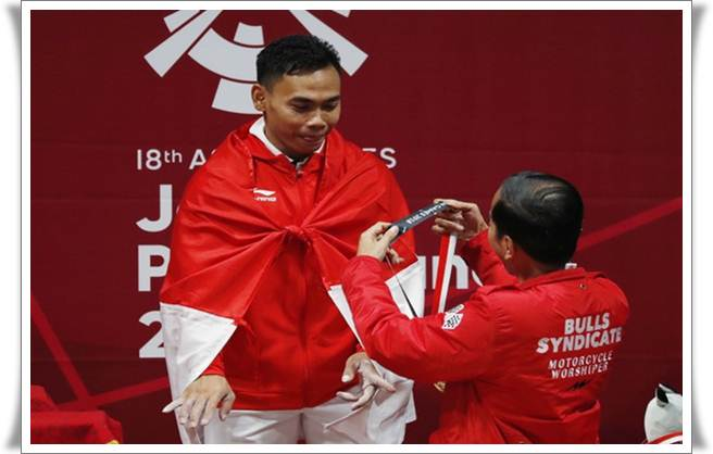 Lifter angkat besi Eko Yuli Putra menerima kalungan medali emas dari Presiden Jokowi usai memenangkan angkatan 62 kg di cabang angkat besi Asian Games 2018, yang digelar di   JIExpo Hall A, Selasa (21/8) - Reuters