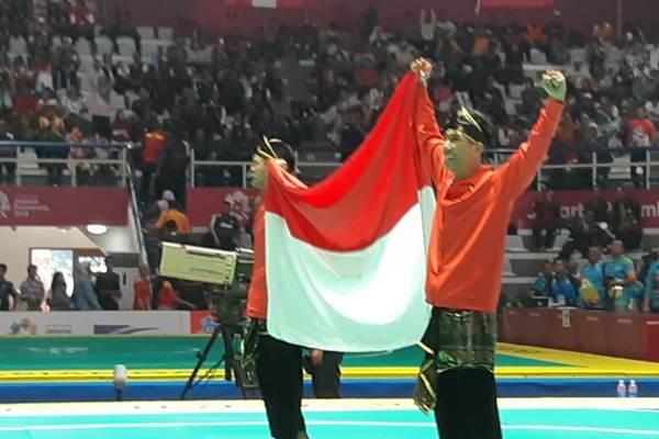 Pesilat ganda putra Indonesia Yola Primadona Jampil dan Hendy mengembangkan bendera Merah Putih usai memastikan merebut medali emas Asian Games 2018. - Bisnis/Yusran Yunus