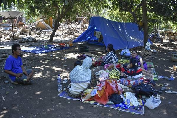 Sejumlah warga beristirahat dekat rumahnya yang roboh pascagempa di Dusun Labuan Pandan, Desa Padak Guar, Kecamatan Sambelia, Lombok Timur, NTB, Senin (20/8). Pascagempa bumi yang berkekuatan 7 Skala Richter mengguncang Lombok pada Minggu malam pukul 22.56 Wita mengakibatkan sejumlah rumah di daerah tersebut roboh dan puluhan warga mengungsi.  - Antara