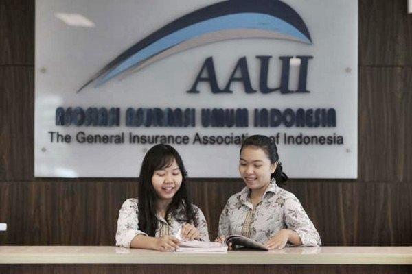 Karyawan berkomunikasi di dekat logo beberapa industri asuransi di kantor Asosiasi Asuransi Jiwa Indonesia (AAJI), di Jakarta. - JIBI/Nurul Hidayat