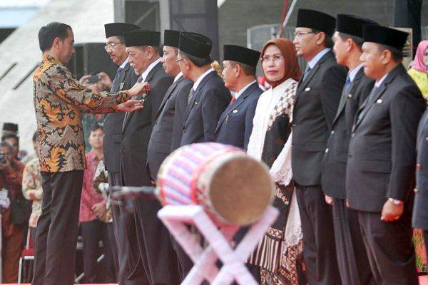 Presiden Joko Widodo (kiri) menyematkan penghargaan kepada Wakil Gubernur Jawa Barat Deddy Mizwar dan sejumlah kepala daerah pada peringatan Hari Koperasi Nasional ke-70, di Makassar, Rabu (12/7). - JIBI/Paulus Tandi Bone