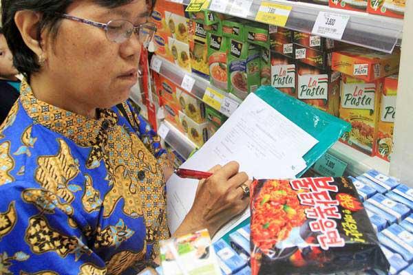 Petugas BPOM memeriksa makanan di salah satu supermarket, di Padang, Sumatra Barat, Minggu (18/6). Razia makanan ini untuk mengantisipasi beredarnya produk mi instan asal Korea yang mengandung bahan minyak babi. - Antara/Muhammad Arif Pribadi