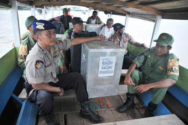 Personel kepolisian bersama anggota Perlindungan Masyarakat (Linmas) membawa kotak suara berisi logistik pilkada dengan kapal kayu menuju wilayah Perairan Pulokerto Gandus Palembang, Sumsel, Selasa (26/6/2018). - ANTARA/Feny Selly