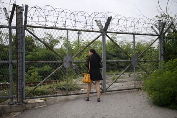 Seorang turis China berada di pagar kawat berduri di Imjingak dekat zona demiliterisasi yang memisahkan kedua Korea, di Paju, Korea Selatan - Reuters