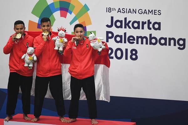 Tim pencak silat Indonesia peraih medali emas Nunu Nugraha (tengah), Asep Yuldan Sani (kiri) dan Anggi Faisal Mubarok (kanan) berpose usai upacara penyerahan medali nomor beregu putra pencak silat seni Asian Games 2018 di Padepokan Pencak Silat Taman Mini Indonesia Indah (TMII), Jakarta, Senin (27/8/2018). - ANTARA/Melvinas Priananda