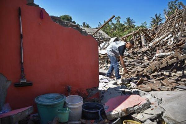 Seorang warga membersihkan puing-puing rumahnya yang roboh pascagempa di Desa Padak Guar, Kecamatan Sambelia, Lombok Timur, NTB, Senin (20/8). - Antara