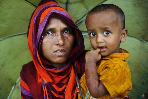 Perempuan pengungsi Rohingya (kiri) menangis sambil menggendong anaknya, saat menunggu bantuan, di Bangladesh, Selasa (19/9). - Reuters/Danish Siddiqui