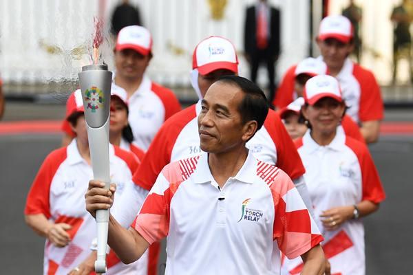 Presiden Joko Widodo (tengah) membawa obor Asian Games XVIII saat prosesi kirab di halaman Istana Merdeka, Jakarta, Jumat (17/8). Sabtu 18 Agustus 2018 api obor akan dibawa estafet menuju Stadion Utama Gelora Bung Karno (SUGBK) menandai dimulainya perhelatan Asian Games XVIII. - Antara