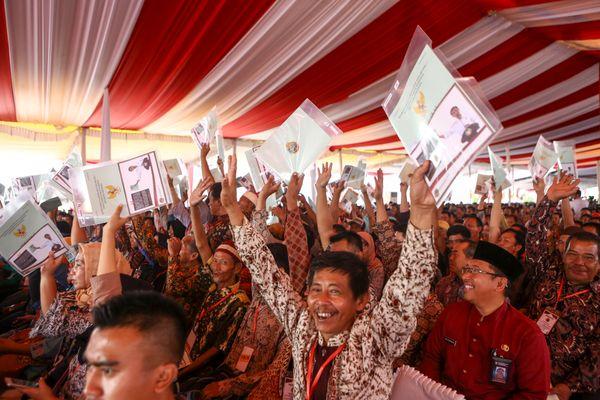 Warga menunjukkan sertifikat tanah saat mengikuti penyerahan sertifikat hak atas lahan tanah oleh Presiden Joko Widodo di pelataran Benteng Kuto Besak (BKB), Palembang, Sumatra Selatan, Jumat (13/7). - ANTARA FOTO/Nova Wahyudi