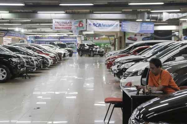 Karyawan sedang menunggu konsumen di samping deretan bursa mobil bekas di Jakarta, Minggu (4/2). - Bisnis.com/Felix Jody Kinarwan