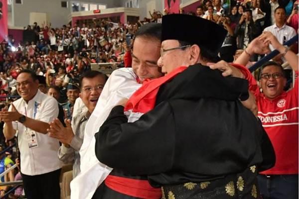 Jokowi dan Prabowo bersama pesilat Hanifan berpelukan dalam selubung bendera Merah Putih - Biro Pers Setpres/ Laily Rachev