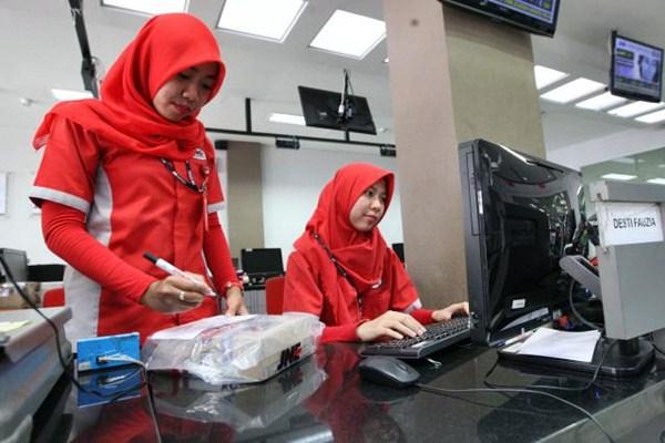 Karyawati PT Jalur Nugraha Ekakurir (JNE) melakukan pendataan paket kiriman. - JIBI/Dedi Gunawan