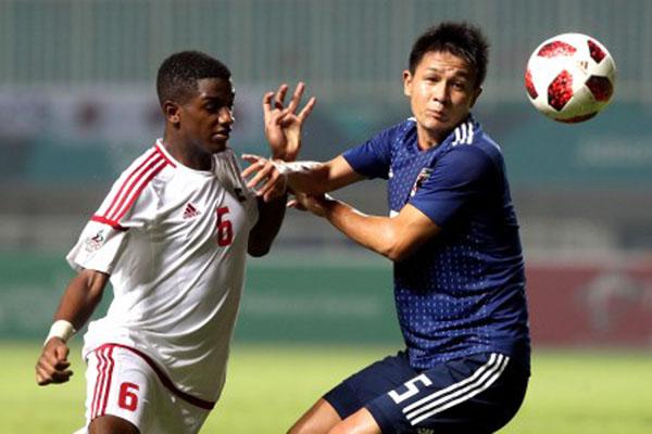 Gelandang UEA Majid Salim (kiri) berebut bola dengan bek Jepang Daiki Sugioka. - Antara